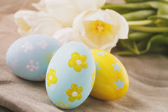 Hand painted easter eggs on table with tulips Stock Images