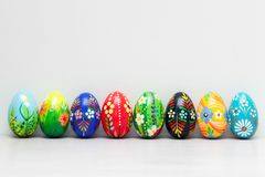 Hand-painted Easter eggs on white rustic wall. Spring patterns Stock Photography