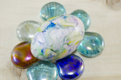 Hand painted egg on colorful pearls Stock Images