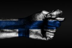 A hand with a painted Finland flag shows a fig, a sign of aggression, disagreement, a dispute on a dark background. Horizontal frame stock image