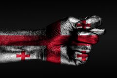 A hand with a painted Georgia flag shows a fig, a sign of aggression, disagreement, a dispute on a dark background. Horizontal frame stock image