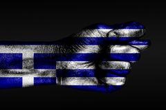 A hand with a painted Greece flag shows a fig, a sign of aggression, disagreement, a dispute on a dark background. Horizontal frame stock photography