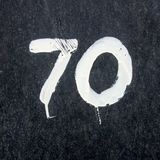 Hand painted house number 70. House  number seventy 70 Hand painted on a marble wall Stock Photo