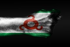 A hand with a painted Ingushetia flag shows a fig, a sign of aggression, disagreement, a dispute on a dark background. Horizontal frame royalty free stock photography