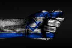 A hand with a painted Israel flag shows a fig, a sign of aggression, disagreement, a dispute on a dark background. Horizontal frame stock image
