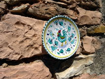 Hand-painted italian porcelain plate hung on a rock wall. Representing a rooster Stock Images