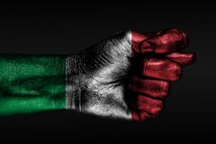 A hand with a painted Italy flag shows a fig, a sign of aggression, disagreement, a dispute on a dark background. Horizontal frame royalty free stock photography