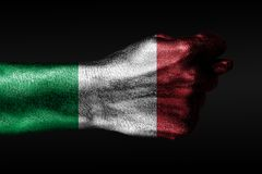 A hand with a painted Italy flag shows a fig, a sign of aggression, disagreement, a dispute on a dark background. Horizontal frame stock photography
