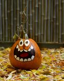 A Hand-Painted Jack-O-Lantern with Dried Leaves in the Foreground royalty free stock photos