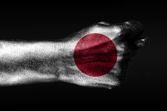 A hand with a painted Japan flag shows a fig, a sign of aggression, disagreement, a dispute on a dark background. Horizontal frame royalty free stock photo