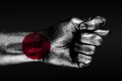 A hand with a painted Japan flag shows a fig, a sign of aggression, disagreement, a dispute on a dark background. Horizontal frame stock photos