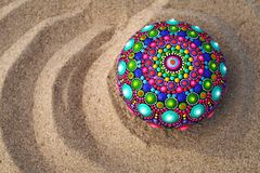 Hand painted mandala rock on sand. Closeup Stock Photography