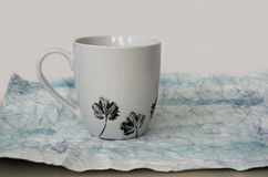 Hand painted mug. White hand painted mug with floral pattern on hand made paper Stock Photos