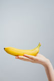 Hand with painted nails clutching a banana Royalty Free Stock Photos
