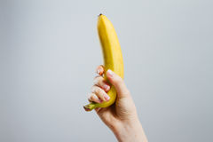 Hand with painted nails clutching a banana Stock Image