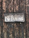 Hand painted NO PARKING sign on weathered wooden door stock photos