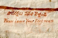 Shoe sign, Hindu Temple, India. Hand painted sign in English and Telugu asking visitors to an historic Hindu temple to remove their shoes.  Golcanda Fort Stock Photos