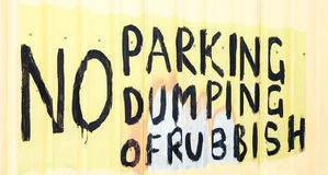 Hand-Painted Sign: NO PARKING DUMPING OF RUBBISH. Hand-painted black, yellow, peach and grey sign on peach-colored fence stating: NO PARKING, NO DUMPING OF royalty free stock photos