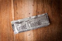 Hand painted sign on wooden door saying gone mining royalty free stock photography