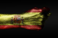 A hand with a painted Spain flag shows a fig, a sign of aggression, disagreement, a dispute on a dark background. Horizontal frame stock image