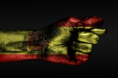 A hand with a painted Spain flag shows a fig, a sign of aggression, disagreement, a dispute on a dark background. Horizontal frame royalty free stock photos