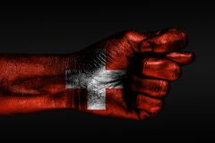 A hand with a painted Switzerland flag shows a fig, a sign of aggression, disagreement, a dispute on a dark background. Horizontal frame royalty free stock image