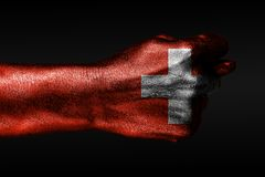 A hand with a painted Switzerland flag shows a fig, a sign of aggression, disagreement, a dispute on a dark background. Horizontal frame royalty free stock photo