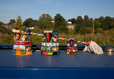 Hand painted traditional decorated watering cans. Canal life in England with traditionally decorated tools on display royalty free stock photo