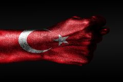 A hand with a painted Turkey flag shows a fig, a sign of aggression, disagreement, a dispute on a dark background. Horizontal frame royalty free stock photo
