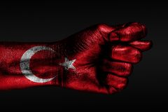 A hand with a painted Turkey flag shows a fig, a sign of aggression, disagreement, a dispute on a dark background. Horizontal frame royalty free stock images