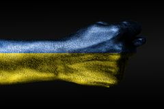 A hand with a painted Ukraine flag shows a fig, a sign of aggression, disagreement, a dispute on a dark background. Horizontal frame stock image