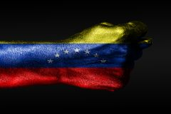 A hand with a painted Venezuela flag shows a fig, a sign of aggression, disagreement, a dispute on a dark background. Horizontal frame royalty free stock photos