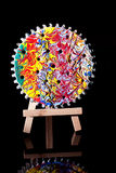 Hand Painted Wooden Gear. A brightly painted wooden gear or cog displayed on a wood easel royalty free stock photography