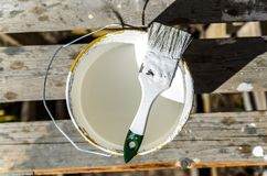 Painter with a brush and a jar of white paint is preparing to paint the house, wall, construction royalty free stock photography