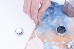 Hand of a painter mixing paint - painting session Royalty Free Stock Photos