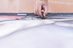 Hand painting a canvas with chalk. Top view of the hand of a painter painting with chalk on canvas - focus on the index finger royalty free stock photo