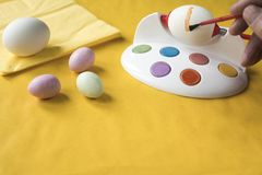 Painting Easter eggs with red brush. stock photo