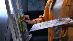 Hand painting the picture with brush from palette. Close up female artist hand with paintbrush applying yellow acrylic paint on almost finished canvas from stock video