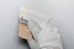 Hand painting a wall in gray Stock Photo