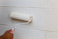 Hand painting wall in white, Repair in a house Stock Photos