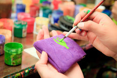 Hand painting a wallet with paintbrush Stock Image