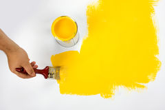 Hand painting yellow. A closeup view of a hand holding a paintbrush and painting a white object yellow Stock Photo