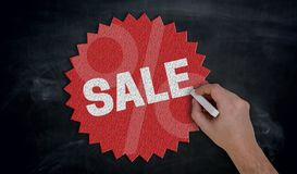 Hand paints with chalk Sale on blackboard Concept royalty free stock photography