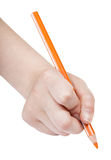 Hand paints by orange pencil isolated. On white background Stock Image