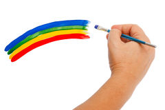 Hand paints a rainbow. On a white background Stock Image