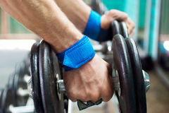 Hand in palm protection grips takes Dumbbell from stand Royalty Free Stock Photography