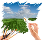 Hand with panit brush painting a beautiful summer landscape Royalty Free Stock Photo