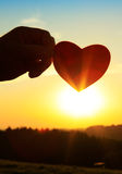 Hand with paper heart at sunrise. Royalty Free Stock Photo