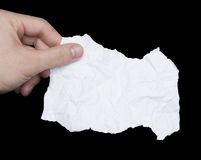 Hand and paper note. Hand holding crumpled torn paper note isolated on black royalty free stock image