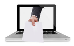 Hand with paper out of laptop Royalty Free Stock Photography